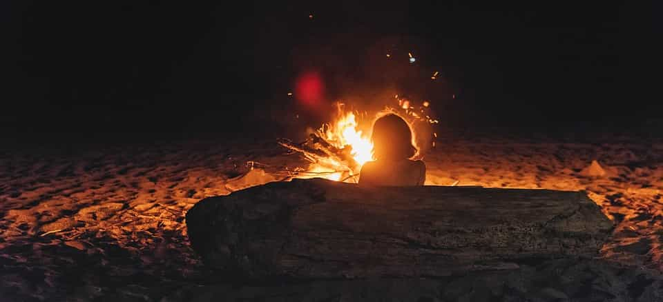 woman sitting beside a bonfire during St. Johns Night