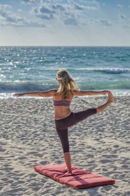 Practicing yoga on the beach